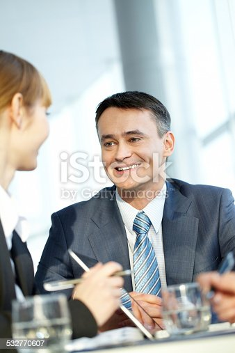 A mature man talking to his female colleague