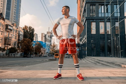 Full-sized portrait of a joyful Caucasian male athlete standing on a city street