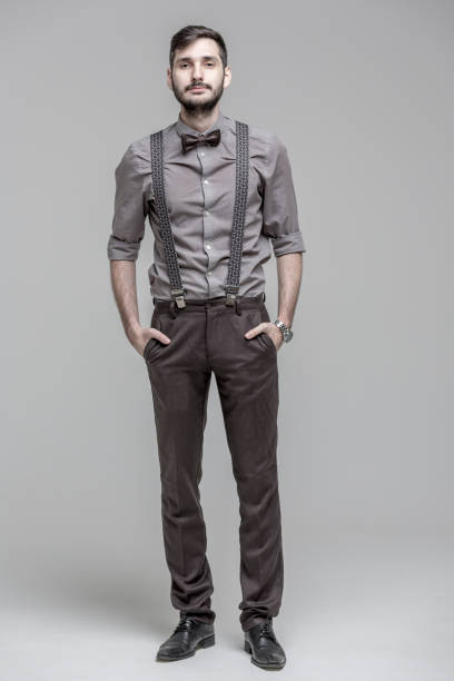 Good-looking Bearded Man Full-length portrait of handsome bearded man dressed in men's classic clothes (shirt, trousers with suspenders and bow tie). The man is standing with hands in pants pockets. He is calmly looking at the camera. Studio shooting on light gray background suspenders stock pictures, royalty-free photos & images