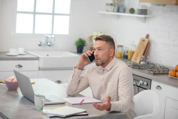 Gutaussehender bärtiger Mann sitzt in der Küche und telefoniert – Foto