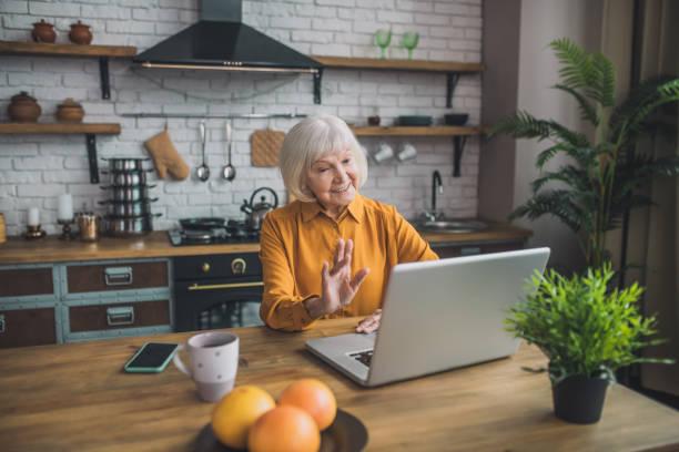 Gutaussehende ältere Dame in gelb mit einem Videoanruf – Foto