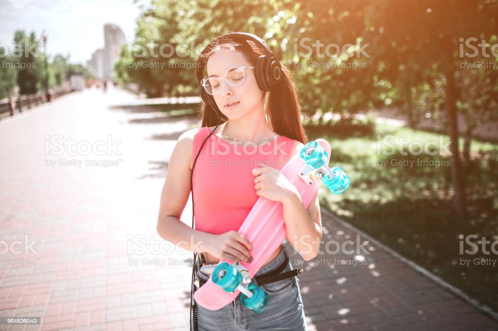 Good-looking girl is standing on street and holding skate in her hands. It is coloured by pink and blue colors. Girl is holding it with both hands and looking down to the side. She is enjoying music royalty-free stock photo
