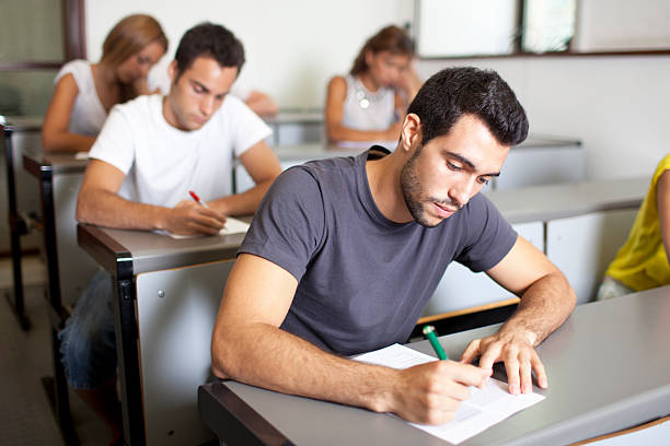Good-looking male student writing an exam stock photo
