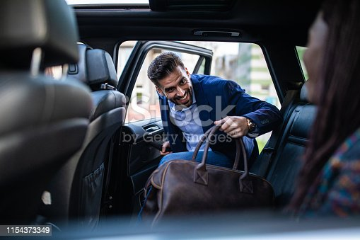 Young, handsome man entering a car, holding luggage, his friends sitting in car and waiting for him