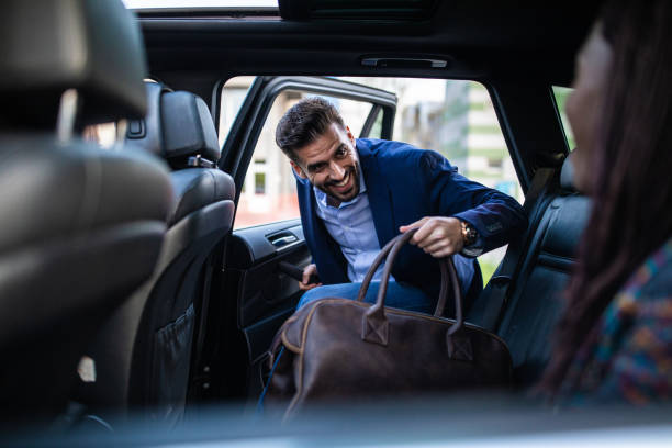 Good-looking man entering ride sharing car Young, handsome man entering a car, holding luggage, his friends sitting in car and waiting for him entering stock pictures, royalty-free photos & images