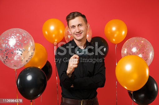 istock Good-looking young man in black classic shirt holding credit card on bright red background air balloons. St. Valentine's International Women's Day Happy New Year birthday mockup holiday party concept. 1126984378