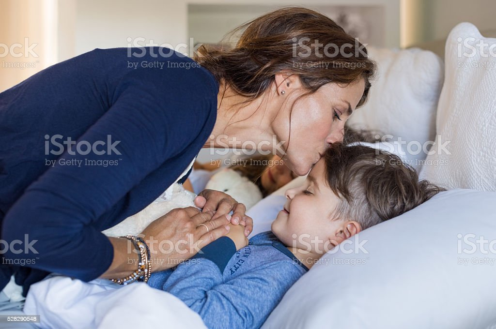 Mother giving good night kiss to sleeping son. Lovely mother putting...