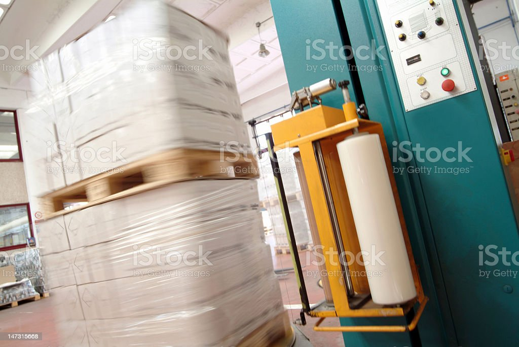 Goods stacked on wood shrink wrapped in industrial packaging royalty-free stock photo
