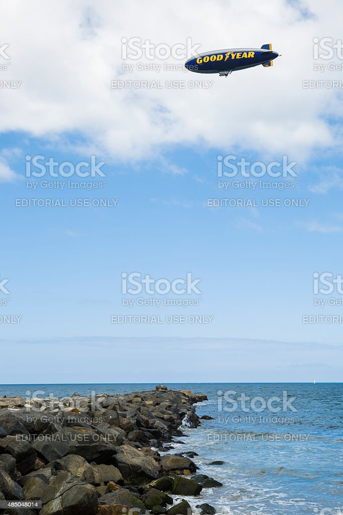 Goodyear Blimp Flying Over Rock Pacific Ocean Shore, Verticle stock photo