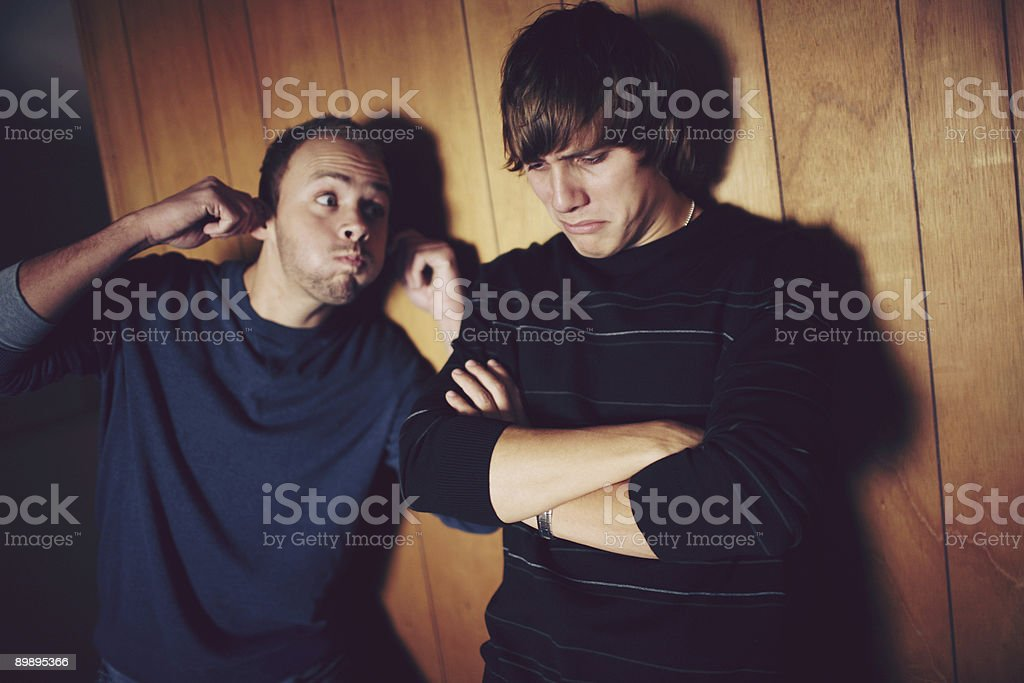 Goofy and Pouty Brothers on Wood Paneling royalty-free stock photo
