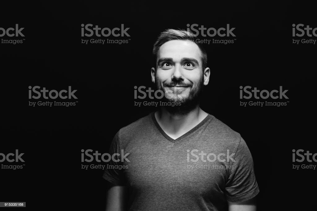 Goofy attractive man squinting his eyes stock photo