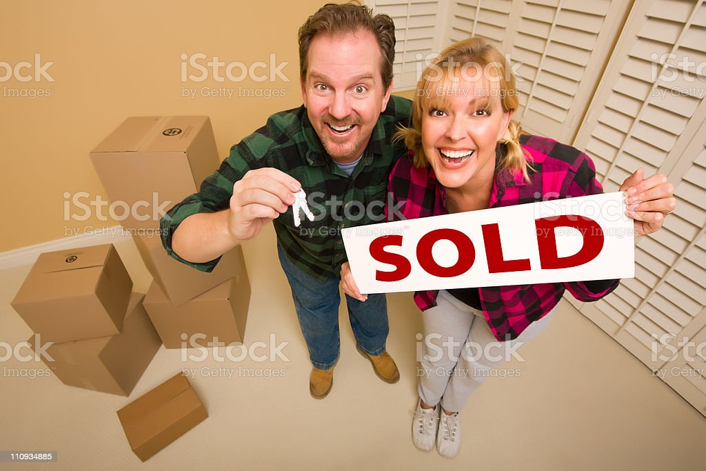 Goofy Couple Holding Key and Sold Sign Surrounded by Boxes royalty-free stock photo