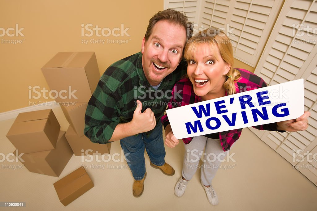 Goofy Couple Holding We're Moving Sign Surrounded by Boxes royalty-free stock photo