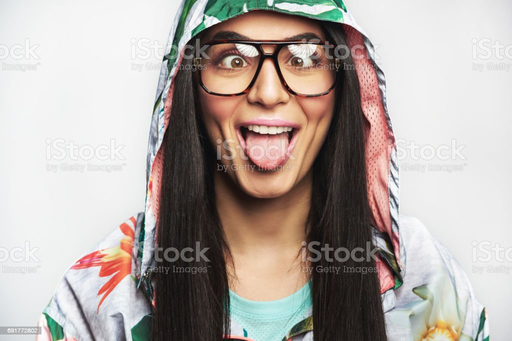 Goofy woman squinting and sticking out her tongue stock photo