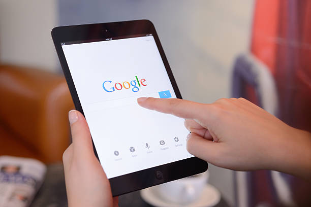 """Google on iPad Mini """"stanbul, Turkey - January 25, 2013: Womans hands holding a iPad Mini displaying Google Application in a coffee shop. iPad is a touchscreen tablet pc produced by Apple Inc."""" google stock pictures, royalty-free photos & images"""