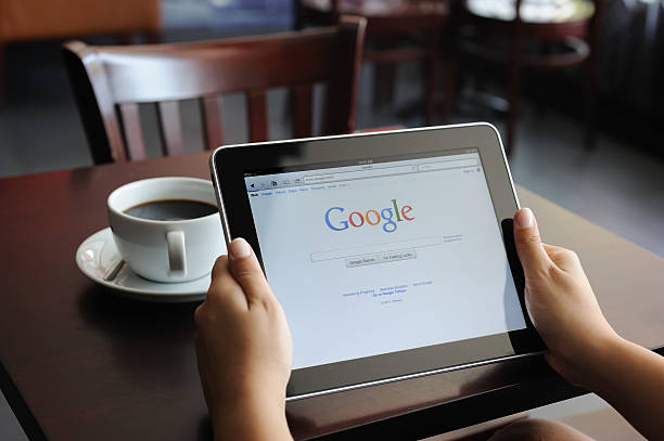 Google on iPad Astanbul, Turkey - July 15, 2011:Hand holding a digital tablet with Google site.Google Inc. is an American multinational public corporation invested in Internet search, cloud computing, and advertising technologies. google stock pictures, royalty-free photos & images
