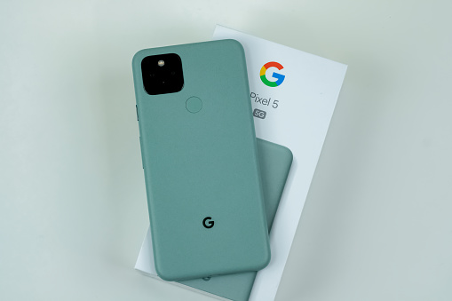 Google Pixel 5 in Sorta Sage color on a white desk after phone with the box and in the hands of the customer. November 11, 2020. Manhattan, NY USA.