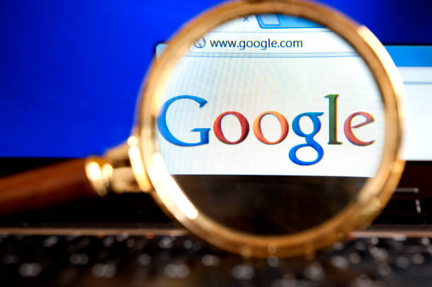 """Google website through a magnifying glass """"Izmir, Turkey - June 11, 2012: Close up to Google  website through a magnifying glass on the laptop. Google is the most popular search engine in the world."""" google stock pictures, royalty-free photos & images"""