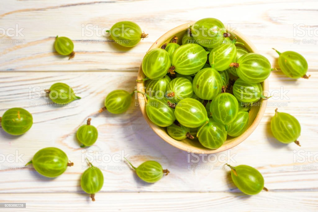 Gooseberry in wooden bowl on white wooden background. Top view with copy space stock photo