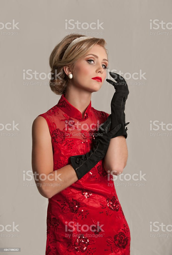 Gorgeous 1950s woman posing with black gloves stock photo