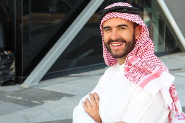 Homem de negócios árabe lindo que sorri no espaço de escritório - foto de acervo