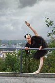 Gorgeous ballerina in black outfit dancing in the city streets