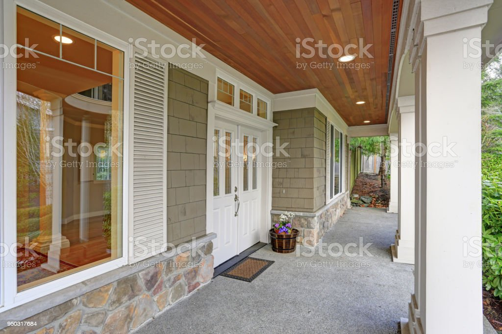 Gorgeous big Craftsman home boasts cozy covered porch with columns.