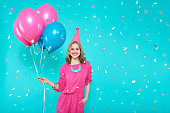 istock Gorgeous birthday girl in party outfit holding colourful balloons. Attractive trendy teenager celebrating birthday. Party and flying confetti on pastel blue background. 941906778