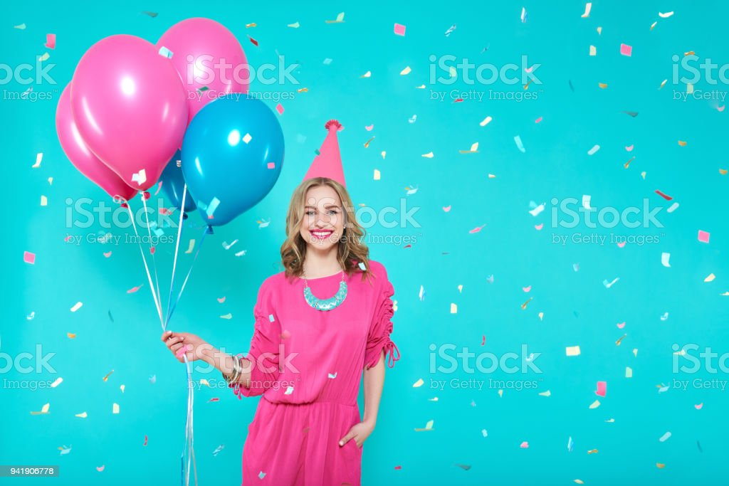 Gorgeous birthday girl in party outfit holding colourful balloons. Attractive trendy teenager celebrating birthday. Party and flying confetti on pastel blue background. stock photo