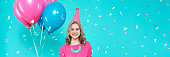 istock Gorgeous birthday girl in party outfit holding colourful balloons. Attractive trendy teenager celebrating birthday. Party and flying confetti on pastel blue background. Web banner. 973846372
