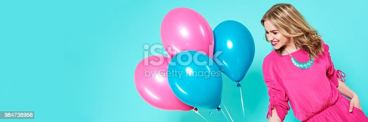 istock Gorgeous birthday girl in party outfit holding colourful balloons. Attractive trendy teenager celebrating birthday. Party concept on pastel blue background. Web banner. 984738956