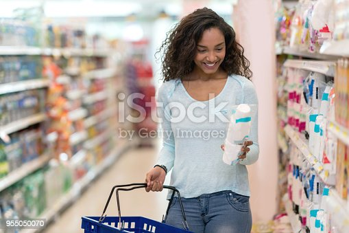 Gorgeous black woman at the supermarket buying products reading the label looking very happy and smiling