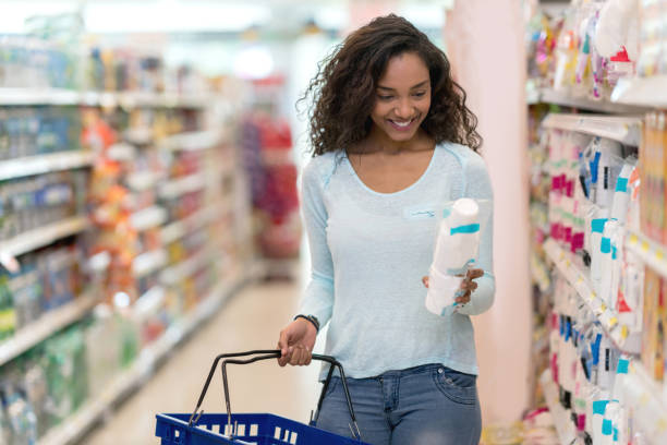 Gorgeous black woman at the supermarket buying products reading the label looking very happy stock photo