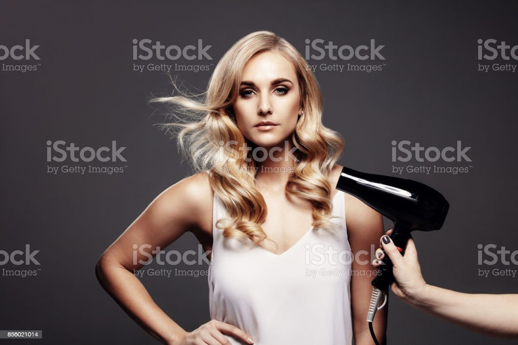 Gorgeous blond woman in a studio with hair dryer stock photo