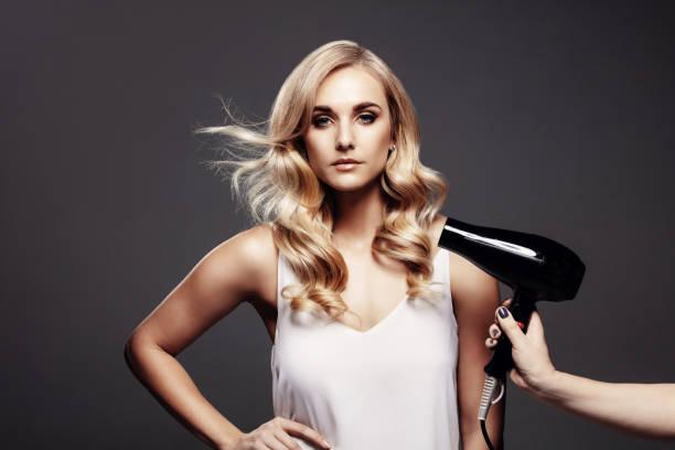 wunderschöne blonde frau in einem studio mit fön - haarfön stock-fotos und bilder