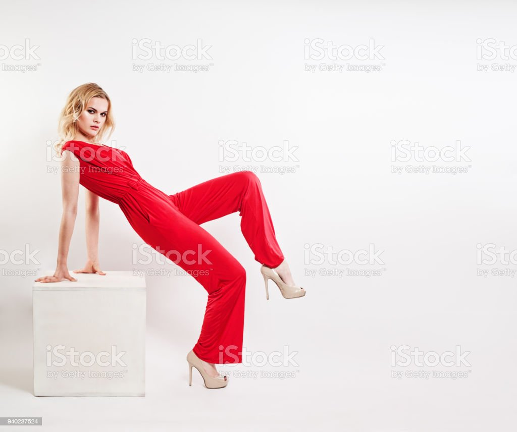 Gorgeous Blonde Fashion Model Wearing Elegant Red Jumpsuit and High Heels Shoes, Fashion Portrait stock photo