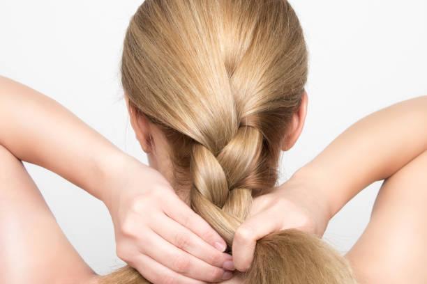 wunderschöne blonde frau zöpfe ihr haar von hinten - zopf frisuren stock-fotos und bilder