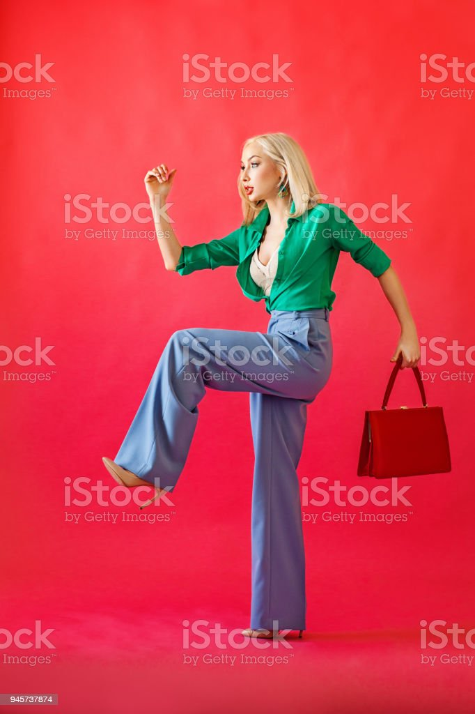 Gorgeous Blonde Woman Fashion Model with Handbag on Red Background. Beautiful Woman Runing to the Goal stock photo