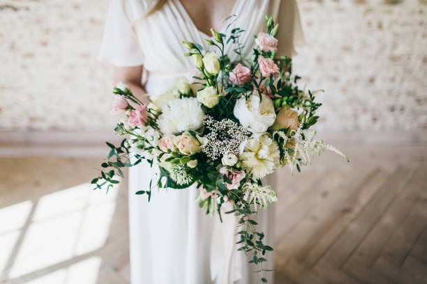 Gorgeous bouquet of white and pink flowers in the hands of the charming bride in a white dress. Artwork – zdjęcie