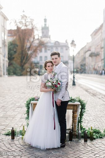 Gorgeous bride and handsome groom standing and hugging near vintage decorated wooden table with flowers and candles on the background.