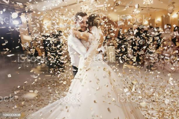 Gorgeous bride and stylish groom dancing under golden confetti at picture id1050000538?b=1&k=6&m=1050000538&s=612x612&h=exgmxl3k8l 6emuyt0raxr uacy7b6rbs0erbyblo2i=