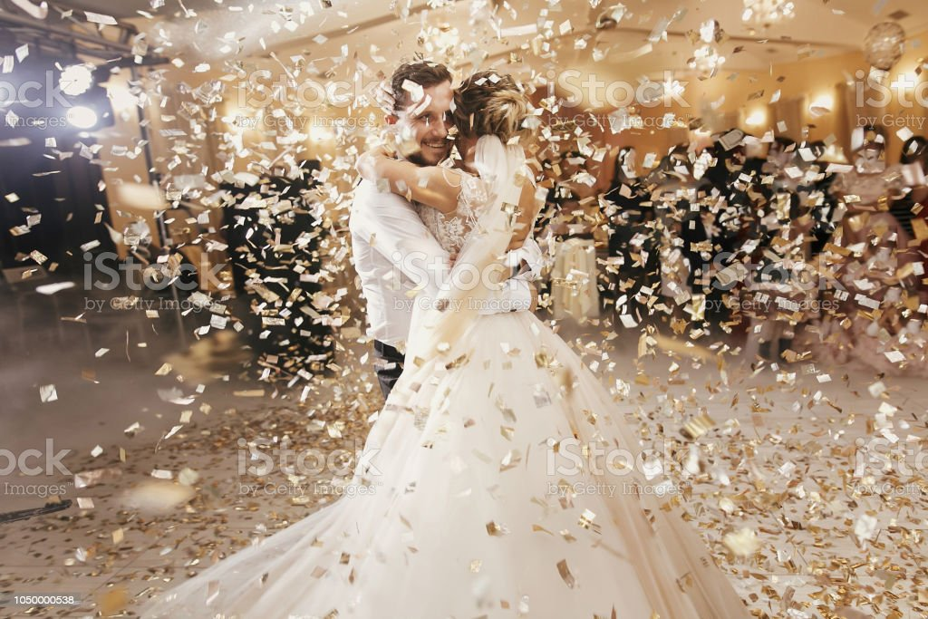 Gorgeous bride and stylish groom dancing under golden confetti at wedding reception. Happy wedding couple performing first dance in restaurant. Romantic moments stock photo