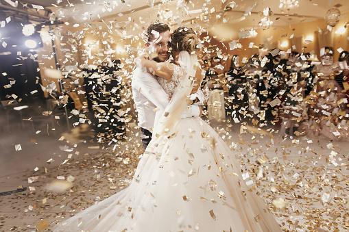 Gorgeous Bride And Stylish Groom Dancing Under Golden Confetti At Wedding Reception Happy Wedding Couple Performing First Dance In Restaurant Romantic Moments - Fotografie stock e altre immagini di Abbracciare una persona