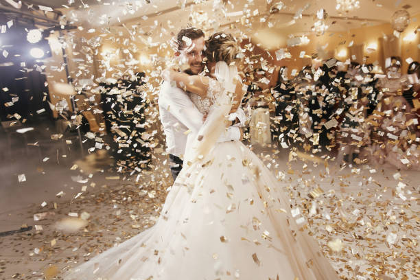 gorgeous bride and stylish groom dancing under golden confetti at wedding reception. happy wedding couple performing first dance in restaurant. romantic moments - wedding stock photos and pictures