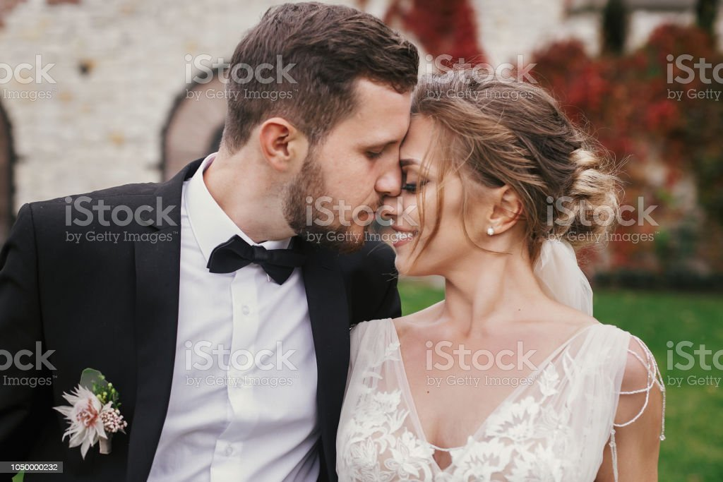 Linda noiva e noivo elegante suavemente abraços e beijos ao ar livre. Casal  de casamento 7bc28a5be24