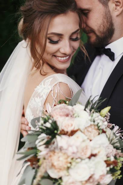 wspaniała panna młoda i stylowy pan młody delikatnie przytulanie i uśmiechając się na tle zielonych drzew. zmysłowa para ślubna obejmując. romantyczne chwile nowożeńców. zdjęcie ślubne - panna młoda zdjęcia i obrazy z banku zdjęć