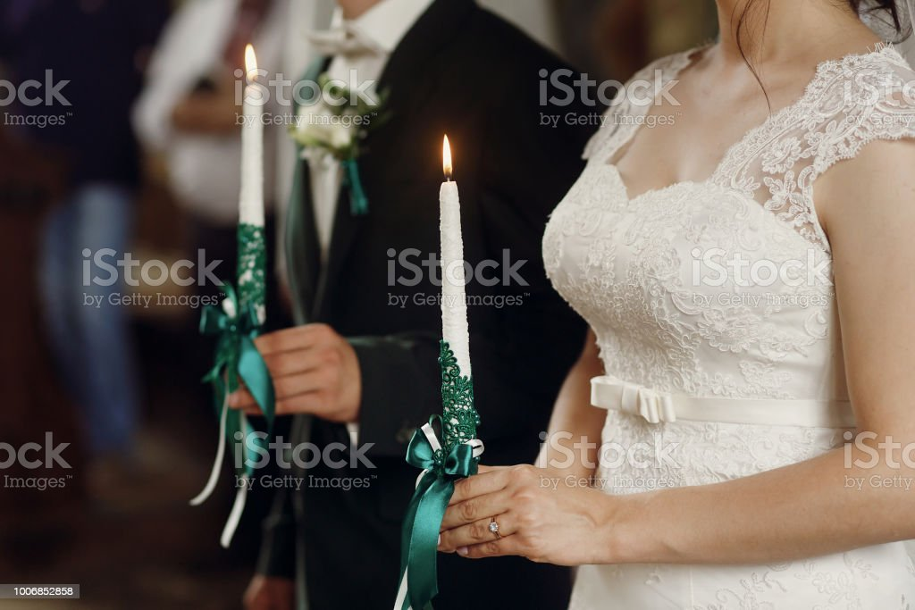 gorgeous bride and stylish groom holding candles at official wedding ceremony in old church. traditional moment stock photo