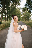 istock Gorgeous bride in elegant wedding dress stand in linden alley with bouquet and posing to photographer 1257516489
