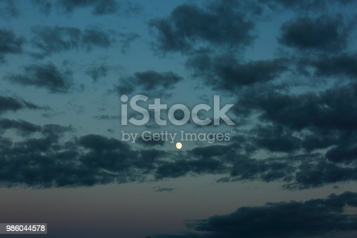 Gorgeous bright moon and few clouds on dark blue night sky. Amazing nature background.
