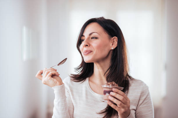 Gorgeous brunette enjoying dessert. stock photo